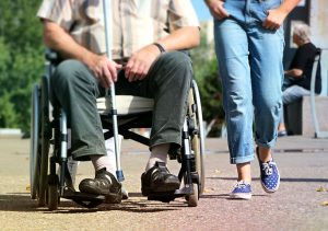 disabled man on a wheelchair accompanied by a health worker